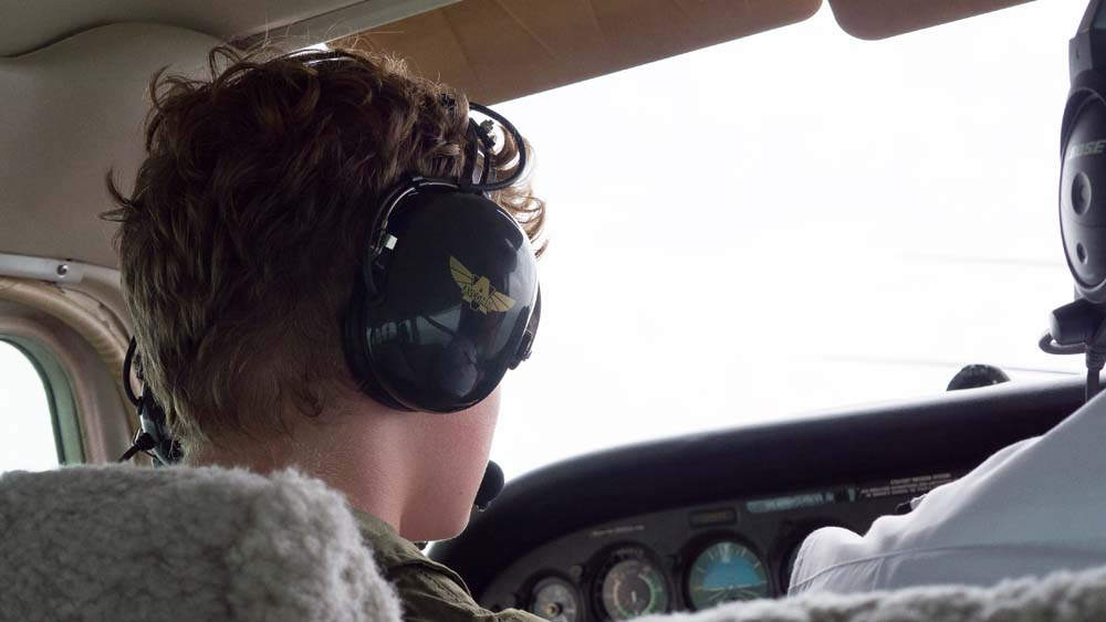 air camp student sitting in cockpit of airplane
