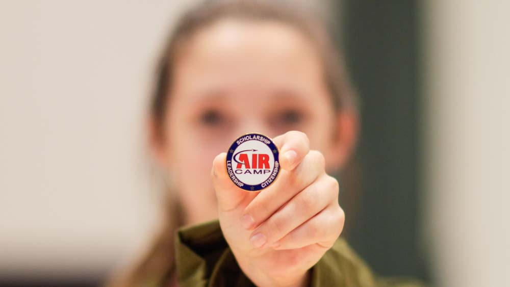air camp student holding an air camp button pin