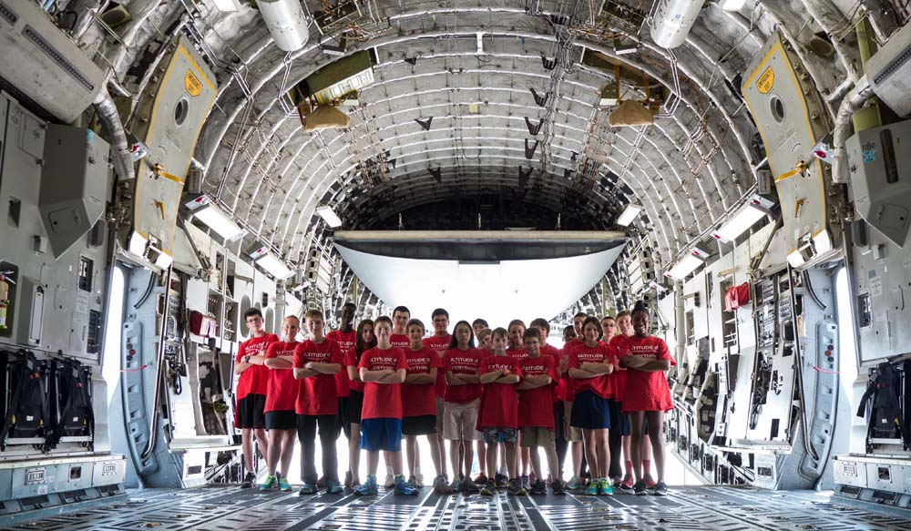 air camp students in storage area of a large plane