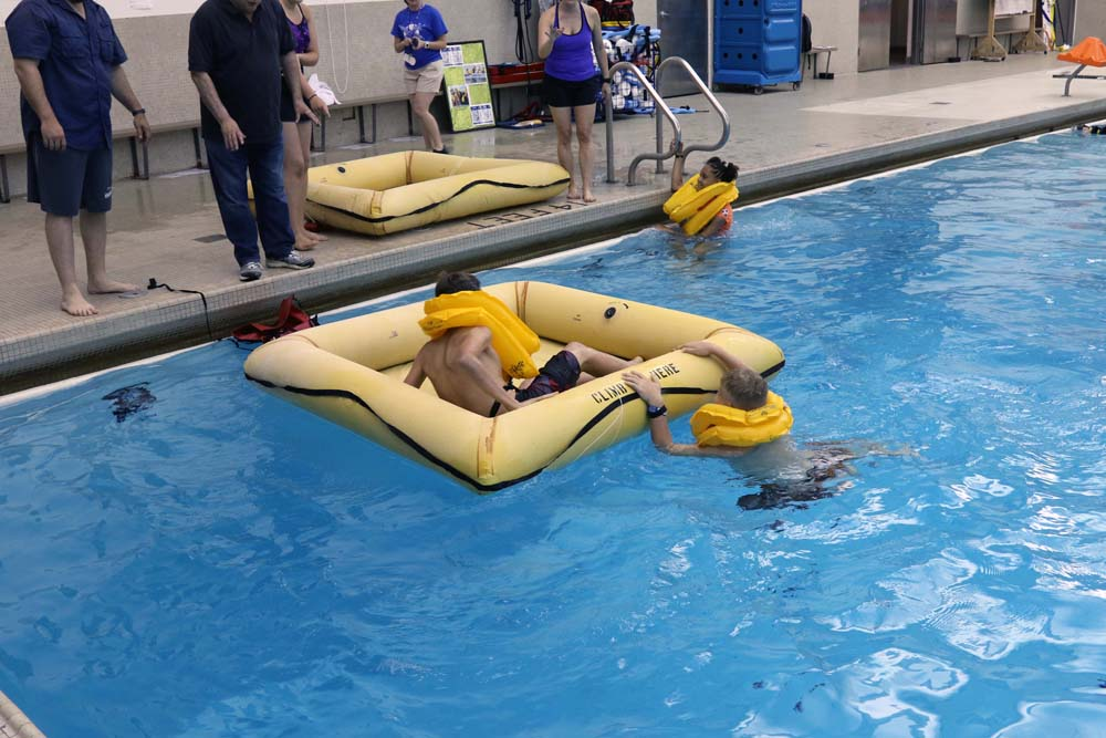 air camp students swimming in pool with a floating boat