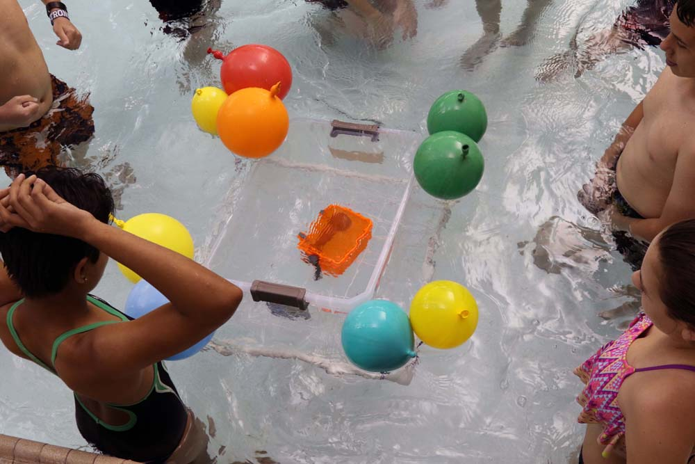 air camp students in pool with balloons trying a science experiment