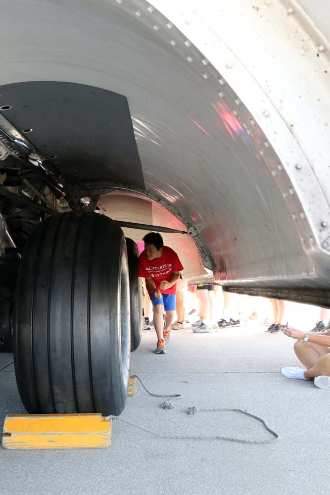 student under an airplane wheel shield