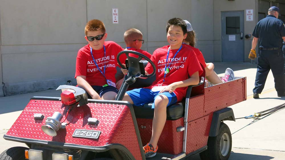 air camp students riding on a cart