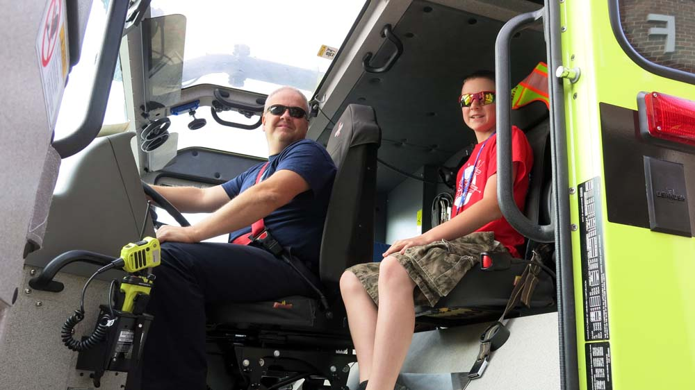 fire fighter and air camp student sitting in a fire truck