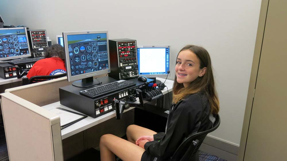 air camp students using an aviation simulator