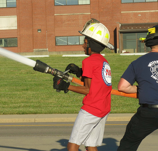 kid using a fire hose with fireman